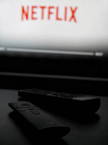 photo of two tv remotes and netflix on the screen in the background